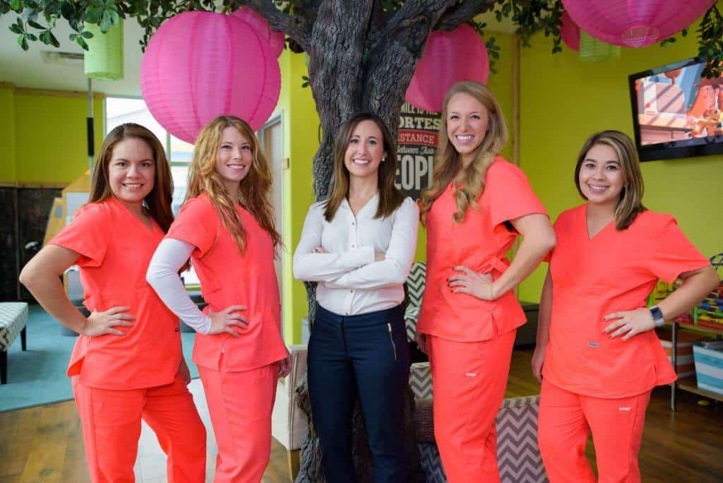 Dr. Erin Saucier DMD, in blue jeans and white button down blouse along with four other team members dressed in orange office uniform, in front of the big tree with the hot pink Chinese lamp balls in the waiting room kids play area of Hill Country Pediatric Dentistry and orthodontics office