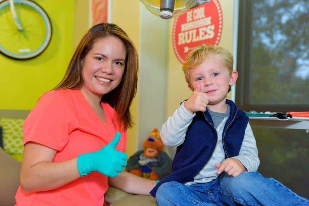 A young patient wearing blue jeans a gray sweatshirt and a blue open zippered vest signaling holding his right thumb up sitting on a treatment bed and a smiling a team members of Hill Country Pediatric Dentistry and orthodontics office wearing orange office uniform and green exam gloves sitting next to the treatment bed on which the blond hair boy is sitting, is also holding her right thumb up the view of the yellow bright wall behind her showing part of the bicycle hanging from the wall