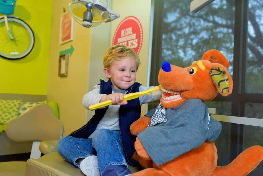 A young patient wearing blue jeans a gray sweatshirt and a blue open zippered vest holding a huge sized yellow tooth brush to brush the teeth of a child size office orange kangaroo stuffed figure who is wearing a gray tee shirt while both are sitting on the treatment bed view of the yellow bright wall behind her showing part of the bicycle hanging from the wall