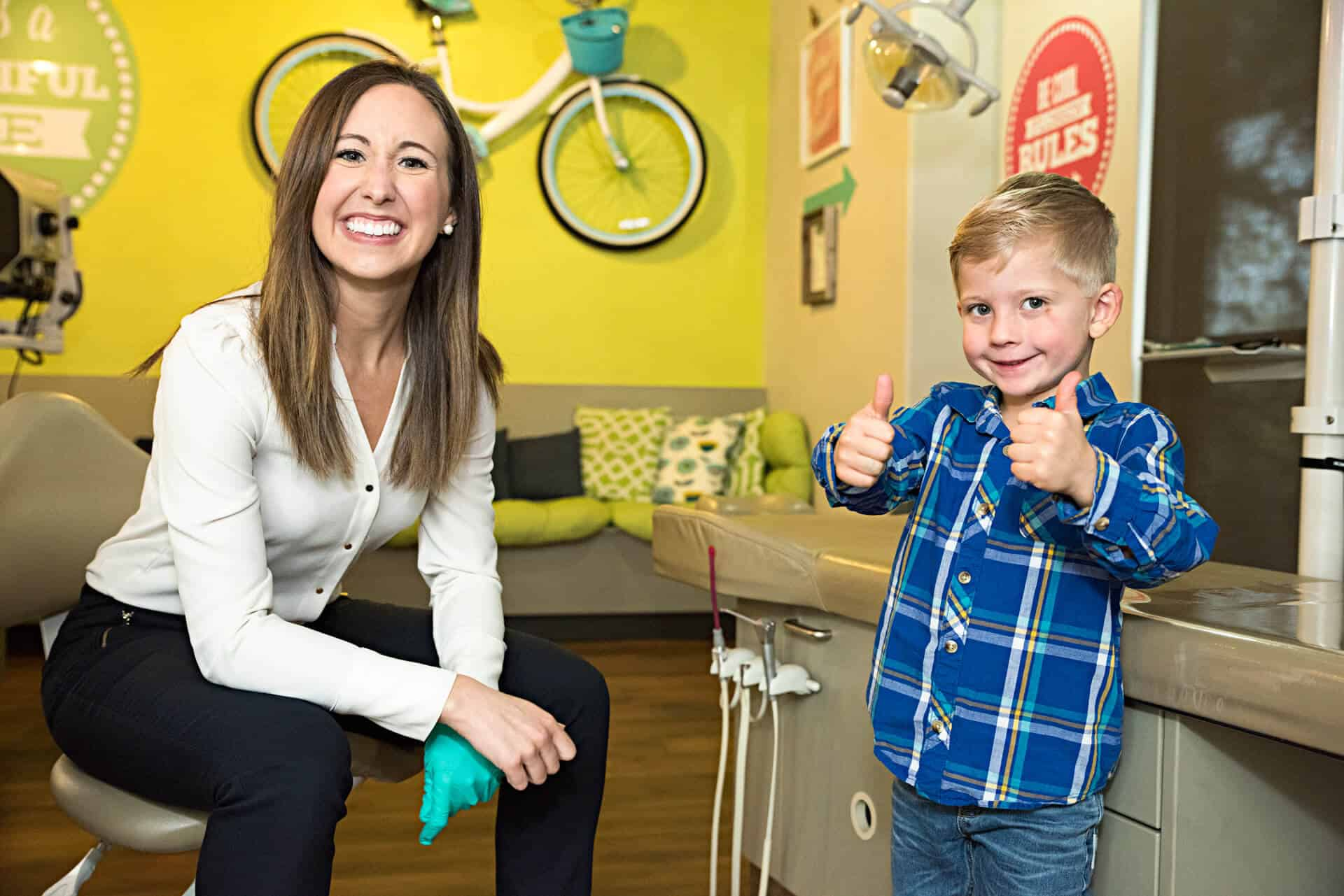 A young patient standing next to the treatment bed wearing blue jeans and a plaid blue flannel shirt smiling and signaling holding both his thumbs up while the dentist  Dr. Erin Saucier dressed in jeans and white blouse is sitting in the doctor chair next to the boy, smiling and leaning forward, her right hand is crossed over  her green exam gloved left hand, the view of the yellow bright wall behind her showing the big real bicycle hanging from the wall next to a retro round lime green sign and the long seating bench covered with lime green base cushion and back cushions in lime green, black and white varied patterns