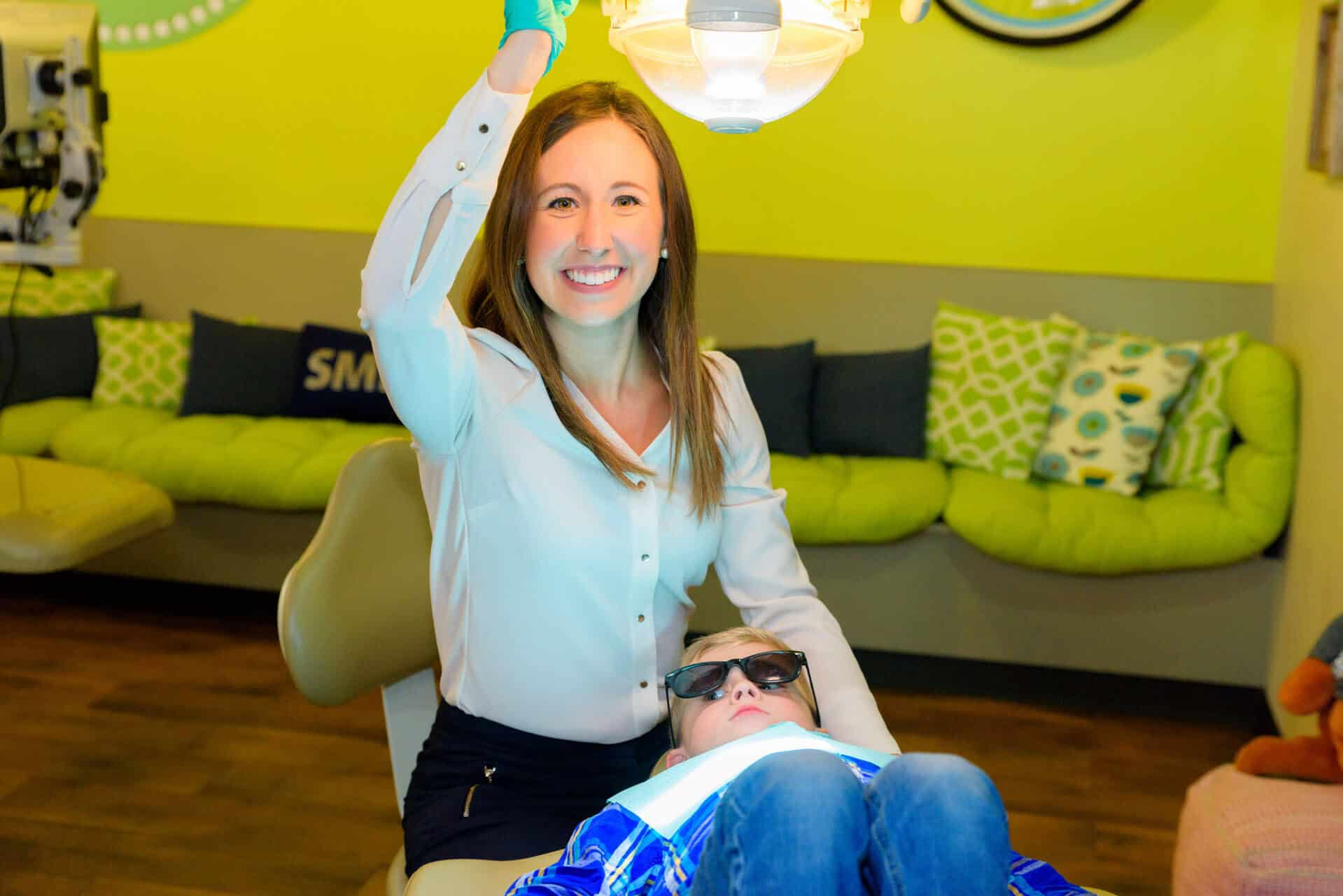 A young patient lying on the treatment bed wearing blue jeans and a plaid blue flannel shirt relaxed while wearing dark glasses over his eyes lying on the treatment bed in the treatment area while the dentist  Dr. Erin Saucier dressed in white blouse is sitting next to the head of the patient bed smiling and reaching up to the light fixture above the boy with her right hand in a green exam glove, the view of the yellow bright wall behind her showing the long seating bench covered with lime green base cushion and back cushions in lime green, black and white varied patterns