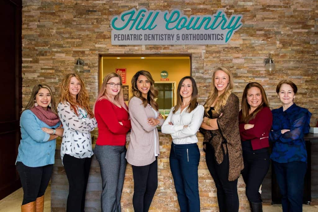 Hill Country Pediatric Dentistry and orthodontics Dental team members with Dr.  Erin Saucier all in casual clothes in a row, four on the left slightly facing towards the right and four on the right slightly facing towards the left, standing in front of the brick wall surrounding the reception window, with the sign of  Hill Country Pediatric Dentistry and orthodontics posted just above the window