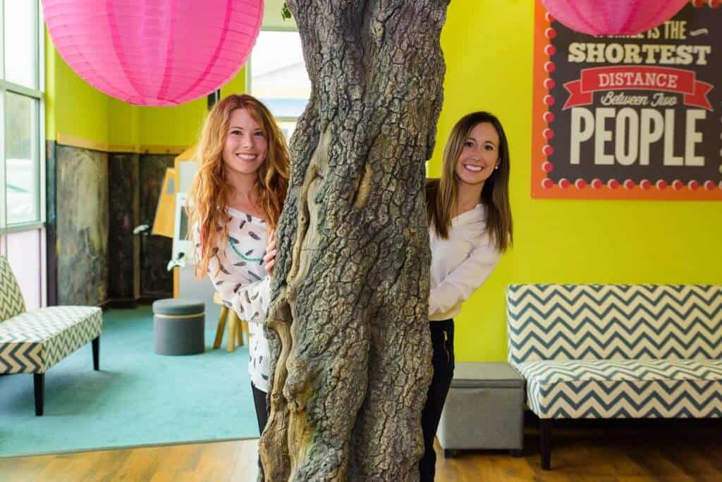 Dr. Erin Saucier DMD, on the right dressed in blue jeans and white button down blouse along with another team member on the left dressed in jeans and a white blouse with a small black leaf pattern print, picking from behind the big tree with the hot pink Chinese lamp balls in the waiting room kids play area of Hill Country Pediatric Dentistry and orthodontics office