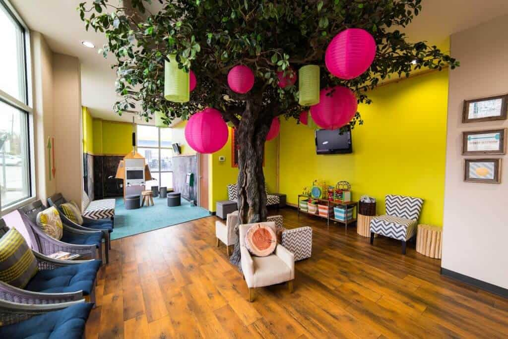 Hill Country Pediatric Dentistry and orthodontics Dental office waiting room and kids play area over view with the big tree with hot pink colored Chinese lamp balls hanging from it in the center of the room chairs in white upholstery around the tree trunk, white rattan chairs with blue seat cushions and lime green back cushion on the left side, a rack with striped design colored bins and activities and toys to the right, and at the far end the game room with blue area rug is visible some walls are colored bright yellow