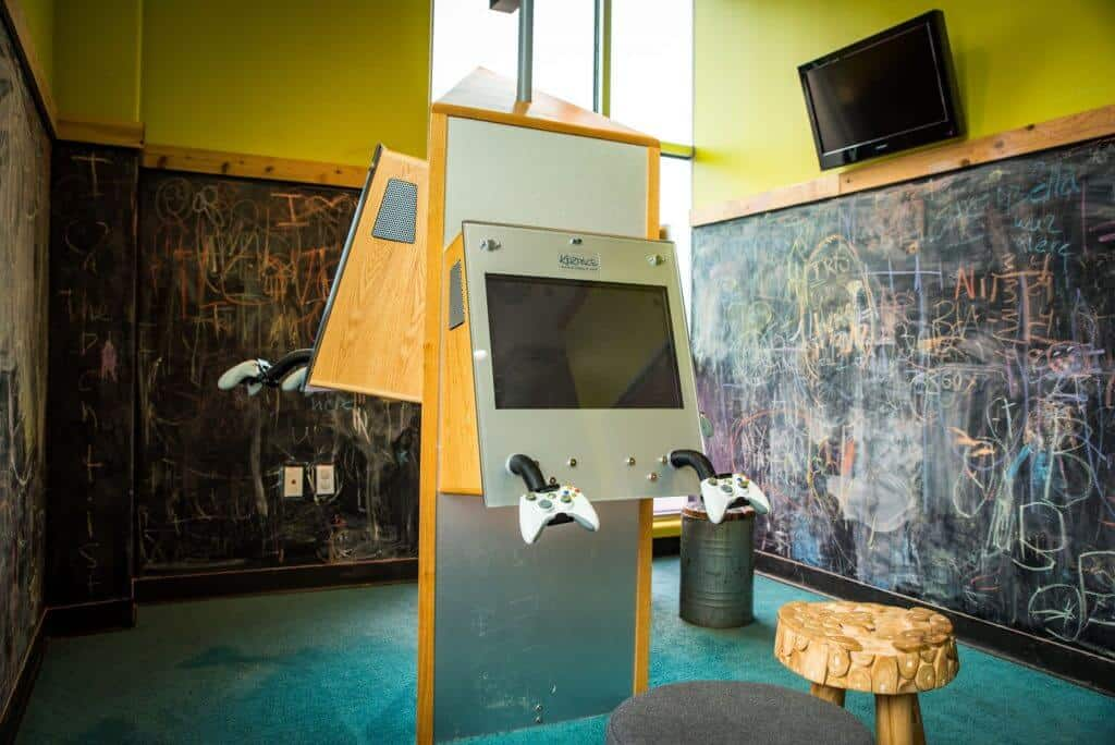 Kids play room with game systems in the center and huge blackboards covering the walls all the way to the floor, TV screen on the top right above one of the blackboards, blue wall to wall carpet and 3 legged stool type chairs