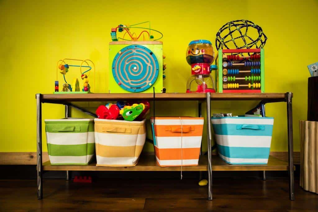 a rack with striped design colored bins and activities and toys against a colored bright yellow wall