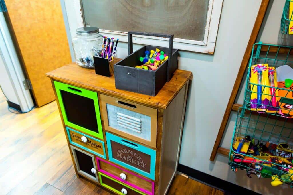 activity center with wood color cabinet with various size ans shape drawers each frames in a different color, some with a white knob and some with a black wide handle