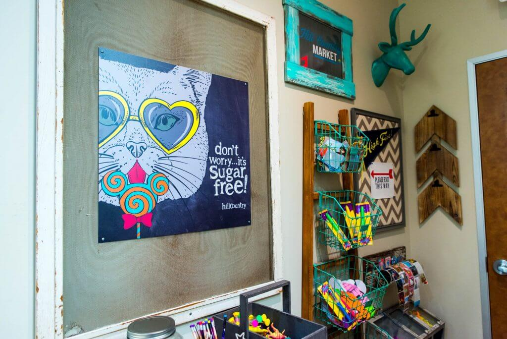activities center rack with teal colored hanging wire baskets, animated character art of a cat with heart shaped lenses yellow glasses frame licking a teal and orange swirled design large flat lollipop saying: don't worry it's sugar free, a deer head in teal color, and a few other original art designs wall hanging